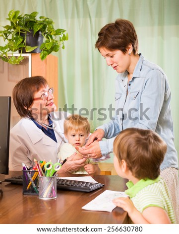 friendly pediatrician doctor examining children with mother at clinic office - stock photo