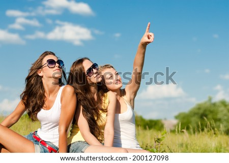 3 friends cute young women beautiful brunette & blond girls sitting in field having fun happy smiling & looking where blonde showing finger on summer outdoors blue sky copy space background portrait - stock photo