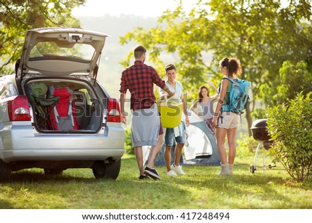 friends unpacking car for camping trip in countryside - stock photo