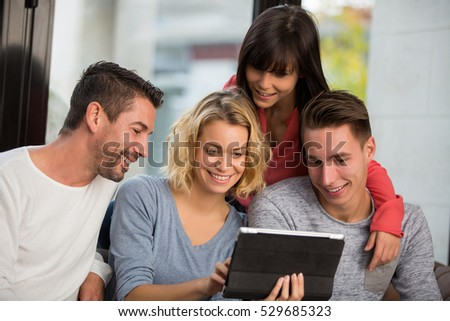 4 friends use digital tablet