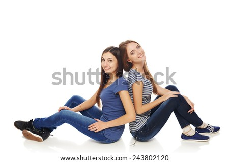 Friendship. Two smiling young girls friends sitting on the white studio floor back to back, isolated on white background.Full length females sitting on a floor and laughing. - stock photo