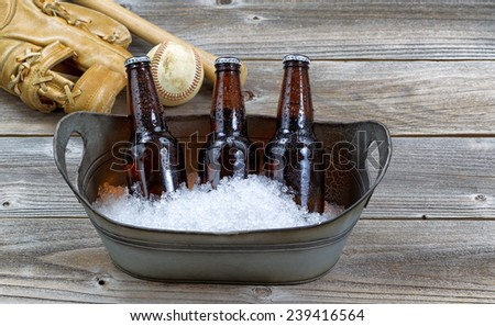 Front view of three brown bottled beers, crushed ice in metal bucket, and baseball equipment in background on rustic wood - stock photo