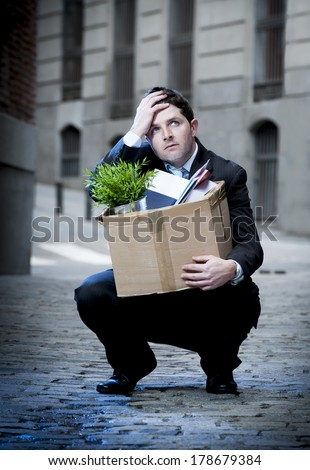 frustrated business man fired in crisis carrying cardboard box on street - stock photo
