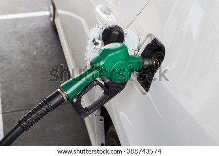 fuel dispenser connecting to the car, add fuel, put in gasoline, benzene, diesel - stock photo
