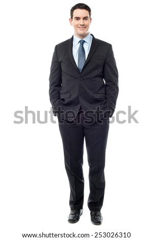 Full length of businessman keeping hands in his pockets