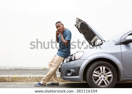 Full length portrait of upset young african man standing in front of a broken car and making a phone call for help - stock photo