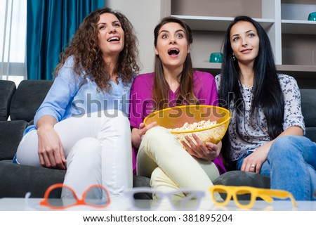Fun Movie with Girlfriends. Three smiling girls eating popcorn while watching a movie on tv with 3d glasses, at home. - stock photo