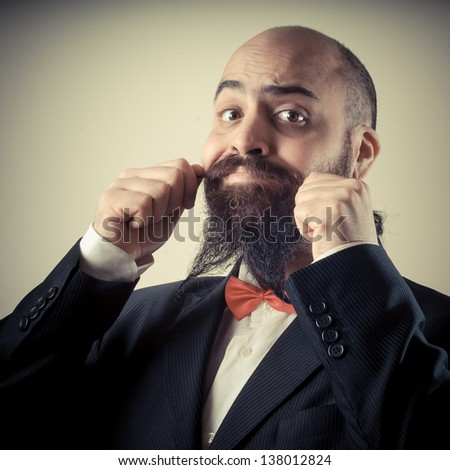 funny elegant bearded man touching mustache on vignetting background
