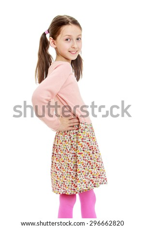 Funny, provocative very skinny little girl with long dark hair braided in a ponytail , in a long cotton dress posing turning to the camera sideways , close-up- isolated on white background - stock photo