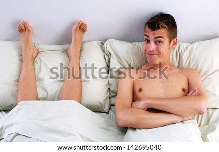 Funny young couple on bed,young man lying down on bed behind wife foot. - stock photo