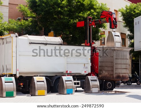 Garbage truck collecting garbage dumpster at city street - stock photo