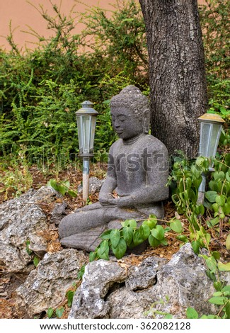 Garden corner whit green leaves Buddha statue and lamps - stock photo