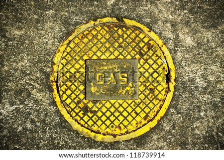 """Gas"" on Manhole Cover,a dirt covered metal manhole cover for a gas supply."