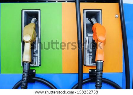 gas pump nozzles - tank - stock photo