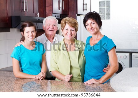3 generation family portrait in kitchen - stock photo
