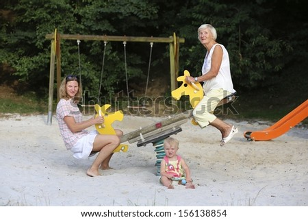 3 generations, a daughter, a mother and a grandmother are having fun on seesaw at a playground - stock photo