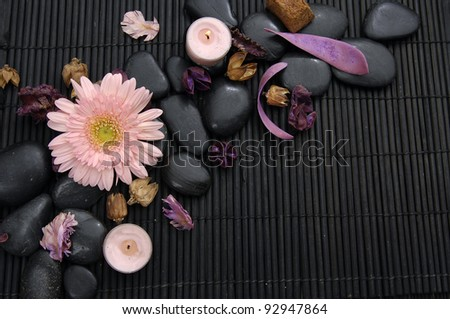 gerbera with flower dried petals and candle on zen stone - stock photo