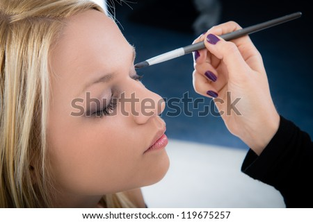 girl applying make-up by make-up artist