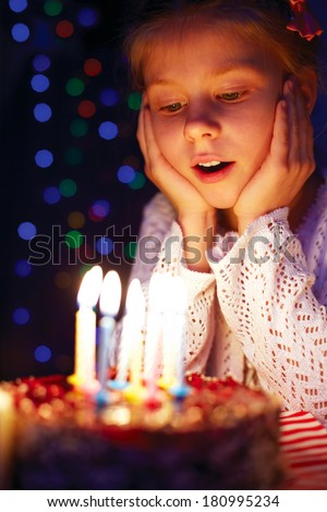 Girl blows out the candles on the cake - stock photo