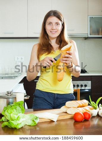 girl cooking sandwiches with  baguette in home kitchen