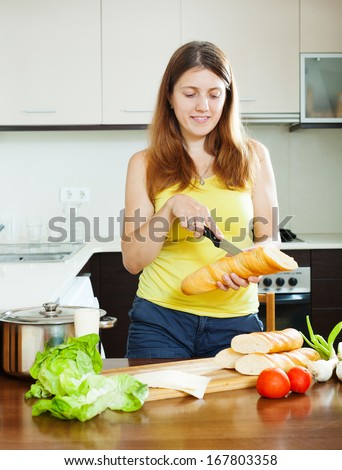 girl cooking sandwiches with  baguette in  kitchen