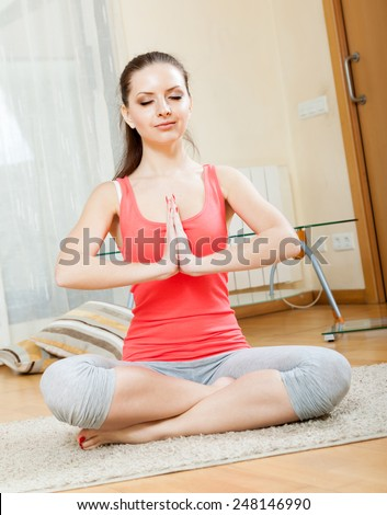 girl doing exercises of  yoga on  mat at home - stock photo