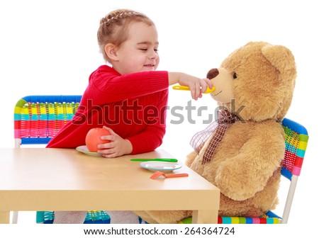 Girl feeding a Teddy bear - isolated on white background - stock photo