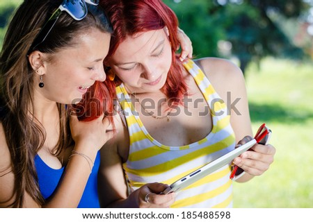 2 girl friends: Two young female students having good fun sitting in park with tablet pc computer on summer day green outdoors background - stock photo