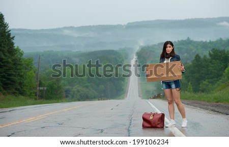 girl hitchhiking holds up a  sign  - stock photo