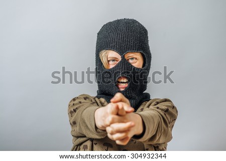 girl in a mask a terrorist  shoots with  finger - stock photo