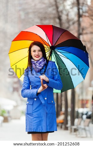 girl in cloak with umbrella in autumn street - stock photo