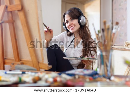 girl in headphones  paints with oil colors on canvas in workshop interior - stock photo