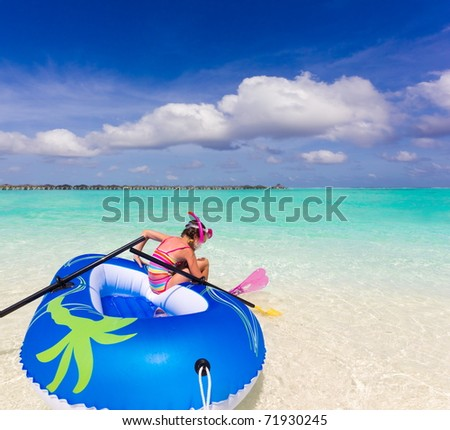 Girl on inflatable dingy in ocean. - stock photo