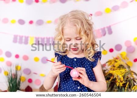 girl paints easter eggs, smiling - stock photo