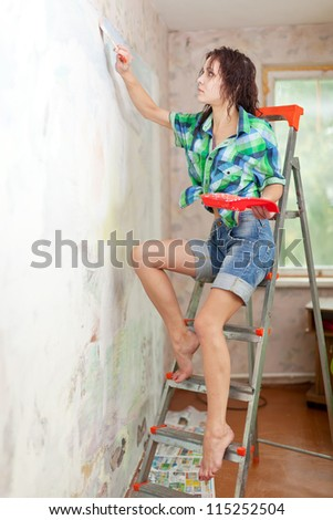 girl paints wall with brush at home - stock photo