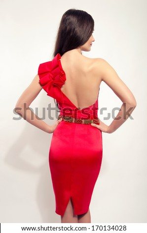 Girl posing fashion in sexy red dress with naked back and tight on the butt. Beautiful brunette woman wearing a one sleeve red dress and holding her hand on her waist. - stock photo