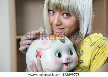 girl saves coins.  coin box-pig - stock photo