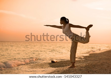 girl silhouette performing yoga on beach during a beautiful sunset