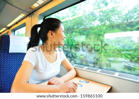 girl sitting on a train and looking out of the window smiling - stock photo