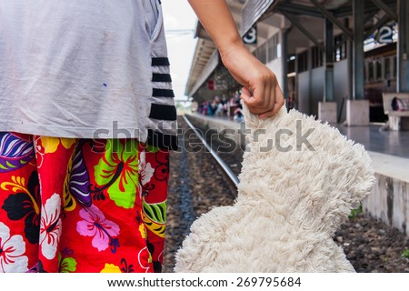 girl standing alone and hand hold white bear at Railway Platform