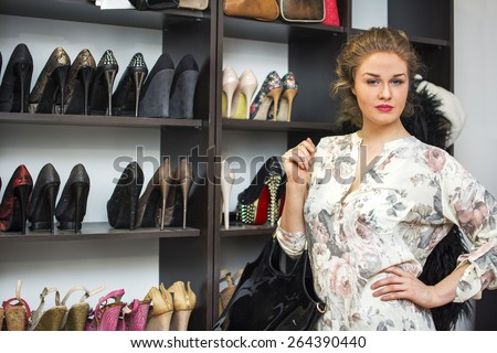 Girl standing in front of shoes in her shoe closet or a shoe store. - stock photo