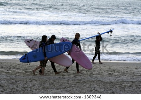 girl surfurs walk on the beach with their boards - stock photo