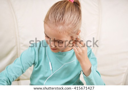 girl using a tablet with headphones sits on couch
