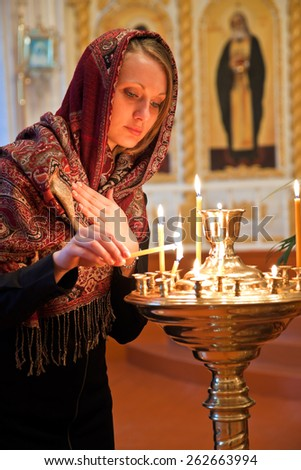 Girl with a candle in the Orthodox Church. - stock photo