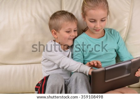 girl with brother using  tablet sits on sofa