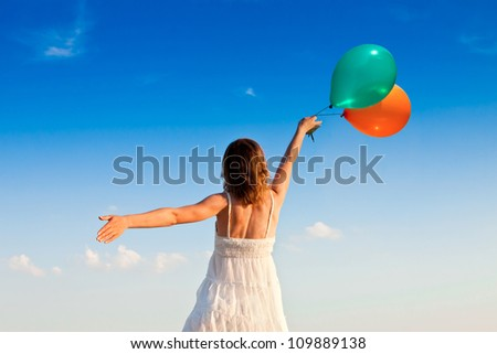 girl with colorful balloons in the sunset light - stock photo