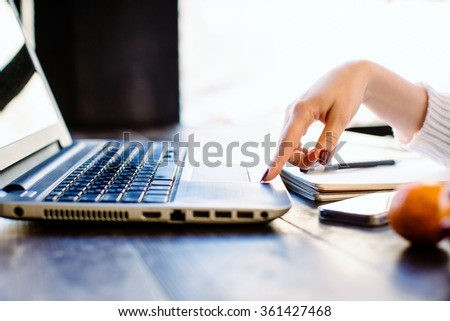 Girl with dark manicure wearing in white sweater touching a laptop, a laptop, mobile phone, mandarin and notebook with a pan on the dark wooden table. Window background.