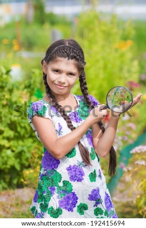 girl with magnifying glass and beetle  - stock photo