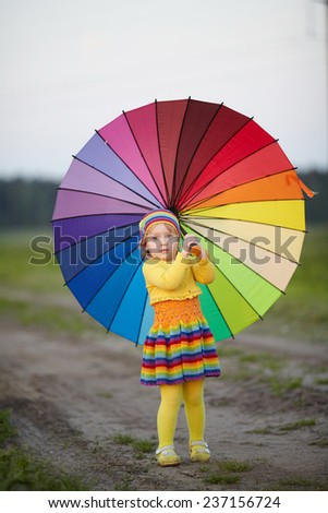 girl with rainbow umrella in the field - stock photo