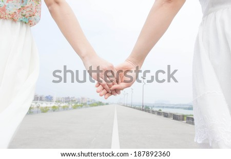 Girlfriends holding hands and walking on the road - stock photo